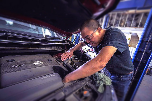 auto mechanic changing oiling in car