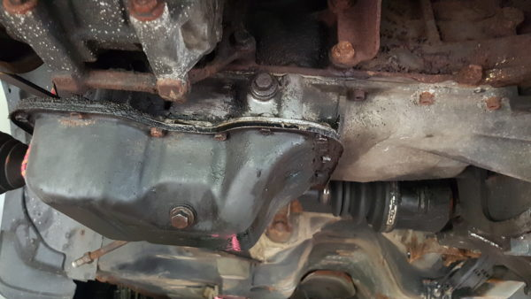 oil pan under a car during an oil change